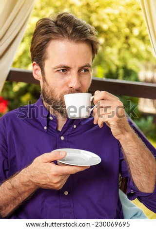 Close up portrait of forty years old caucasian man drinking morning coffee outdoor on garden terrace during sunny summer day. Countryside weekend or holiday concept. - stock photo