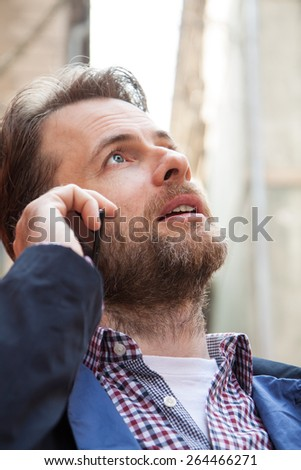 Close up portrait of forty years old caucasian man in casual clothes talking on a mobile phone. City buildings as background. - stock photo