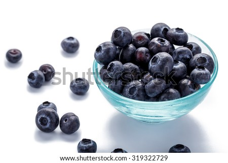 close up portrait of fresh blueberries in a glass bowl on white background