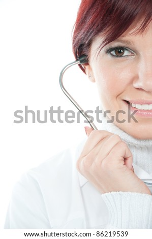 Close-up portrait of friendly female doctor smiling and holding a stethoscope, isolated over white - stock photo