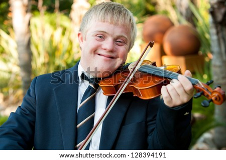 Close up portrait of friendly handicapped boy playing violin outdoors. - stock photo
