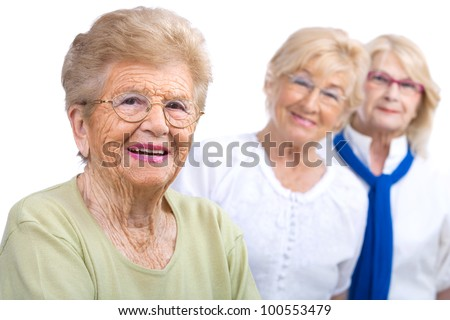 Close up portrait of friendly senior woman with girlfriends in background.Isolated on white. - stock photo