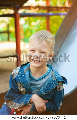 Close up portrait of funny smiling child face. 7 years old kid playing at children playground. Caucasian blond boy dressed in casual denim clothes. Happy kid sitting on slide on spring or summer day. - stock photo