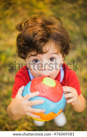 Close up portrait of funny toddler boy playing with toy plastic boy outdoors on sunny summer evening. Sunset vertical image portrait of cute little child. Top view.