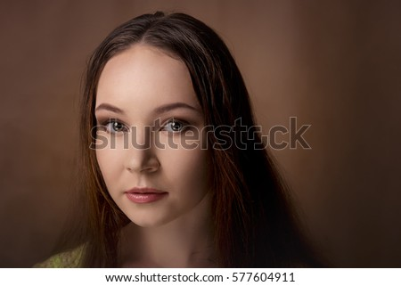 Close-up portrait of girl isolated on a brown background with professional makeup