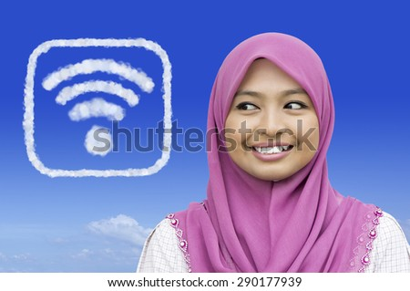 Close-up portrait of girl looking to full coverage wireless network icon in blue sky - stock photo