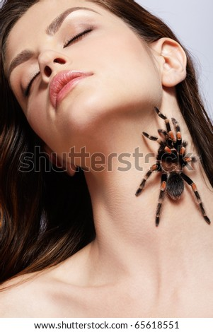 close-up portrait of girl with brachypelma smithi spider creeping over her neck