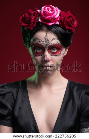 Close-up portrait of girl with Calaveras makeup and a red flower in her black hair frustrated looking at you isolated on red background with copy place - stock photo