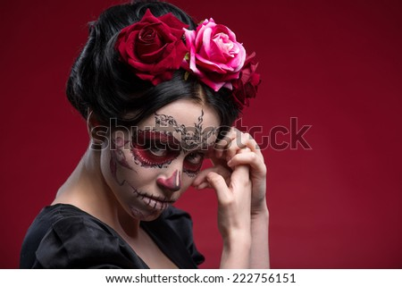 Close-up portrait of girl with Calaveras makeup and a red flower in her black hair looking at you under a forehead and holding her hands near her face isolated on red background with copy place - stock photo