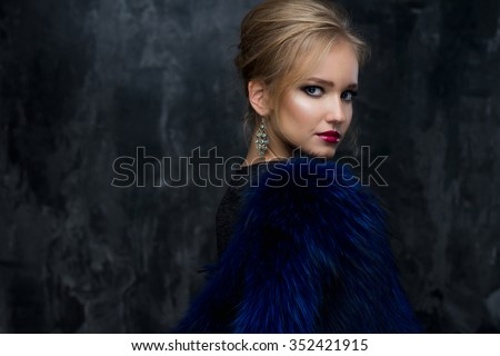 Close-up portrait of gorgeous blonde young woman in celebrity style with perfect make up and hair style wearing blue fur. Fashion beauty photo, dramatic look - stock photo
