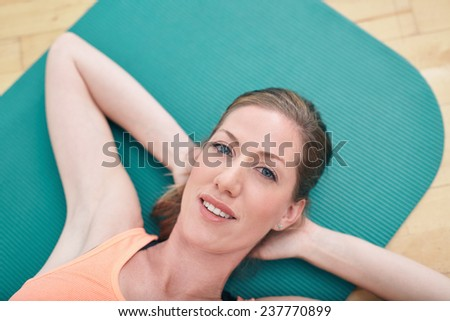 Close-up portrait of gorgeous female smiling while lying on gym floor. attractive fitness woman lying on exercise mat with her hands behind her head looking at camera. - stock photo
