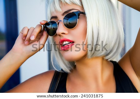 Close up portrait of gorgeous woman in stylish sunglasses  perfect skin , white teeth and red full lips in white short wig. - stock photo