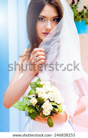 Close up portrait of gorgeous  young woman with bridal veil  and wedding bouquet looking in the camera and smile .