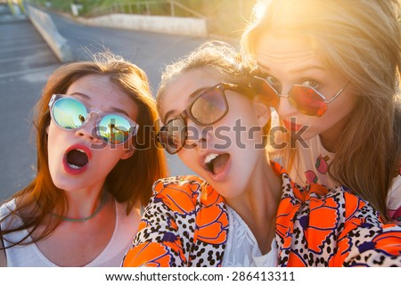 Close-up portrait of group of tree young friends wearing sunglasses,stylish friends,hugging and standing in a row at sunset, spending time with friends.posing on gold sunset,Make self picture  - stock photo