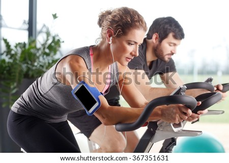 Close-up portrait of gym members participating in a spinning class while training together at fitness center. Sporty woman listening music at her mobile phone.