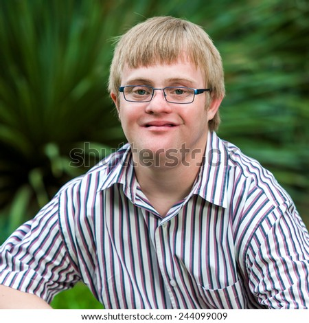 Close up portrait of handicapped boy in garden wearing glasses. - stock photo