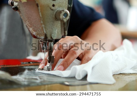 close up portrait of hands of seamstress sewing using industrial sewing machine
