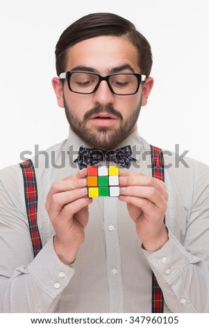 Close-up portrait of handsome boy nerd holding a rubik's cube in front of him. Man looking at rubik's cube isolated on white. - stock photo