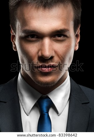 Close-up portrait of handsome business man looking at camera - stock photo