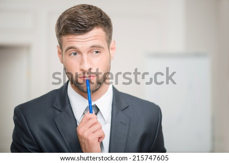 Close-up portrait of handsome businessman in office interior touching his lips with a pen and looking aside and thinking, making some decision with copy place - stock photo