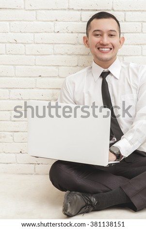 close up portrait of handsome businessman relax sitting on the floor while working on laptop
