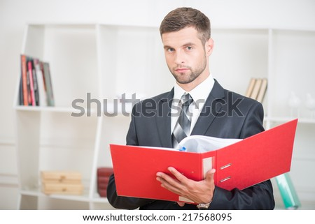 Close-up portrait of handsome confident businessman standing in office with a red folder in his hands and looking at the camera with serious face - stock photo