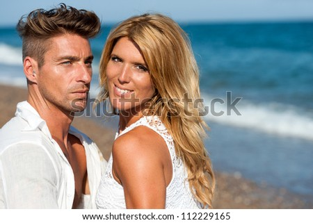 Close up portrait of handsome couple in white on beach. - stock photo