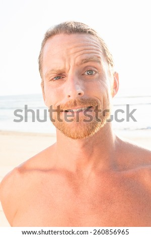 Close up Portrait of Handsome Man with Beard and Mustache at the Beach Looking at the Camera with Confused Face. - stock photo