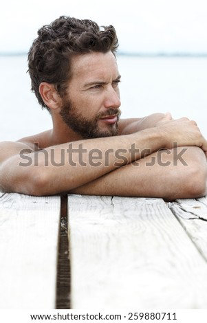 Close up Portrait of Handsome Man with beard and No Shirt Posing at the Sea  - stock photo