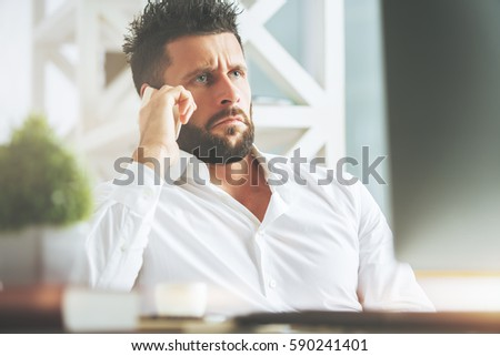 Close up portrait of handsome man with confused expression talking on the phone at workplace