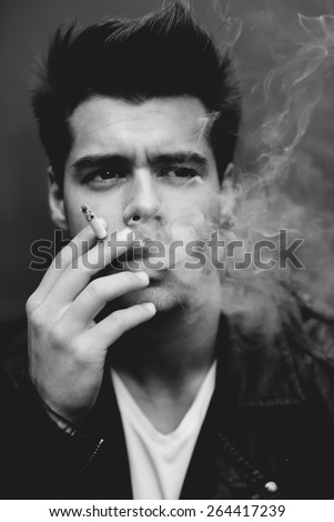 Close up portrait of handsome masculine model smoking cigarette and exhaling the fume, trendy attractive man blowing smoke out of his mouth, black and white filter,vintage effect - stock photo