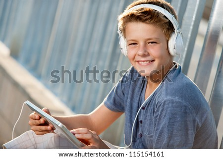 Close up portrait of handsome teen boy with tablet and headphones. - stock photo