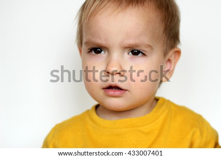 Close-up portrait of handsome toddler boy with interested emotion on his face, indoor portrait - stock photo