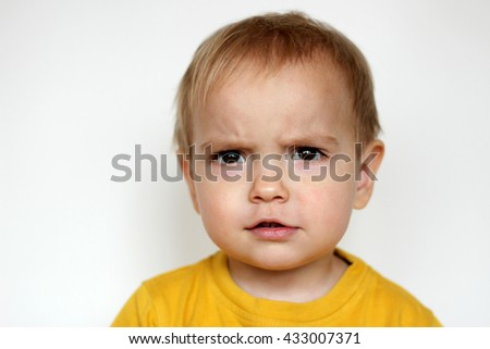 Close-up portrait of handsome toddler boy with interested emotion on his face over white backgrounds, indoor portrait
