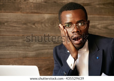 Close up portrait of handsome young African corporate worker who is scared, shocked or astonished by something, holding a hand on his cheek, mouth wide open. Human face expressions and emotions