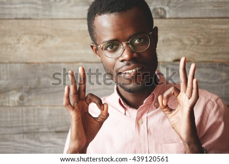 Close up portrait of handsome young man looking and smiling at the camera, gesturing 'OK' sign with both hands, showing that everything is great. Positive human emotions and facial expressions - stock photo