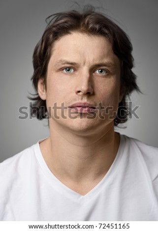 Close-up portrait of  handsome young man with serious face looking at camera - stock photo