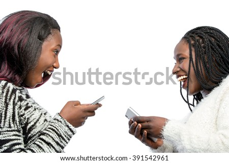 Close up portrait of happy african teen girls laughing with smart phones. Isolated on white background.