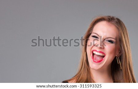 Close-up portrait of  happy beautiful gir over gray background. Copyspace image - stock photo