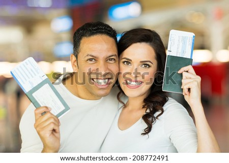 close up portrait of happy couple holding passport and boarding pass - stock photo