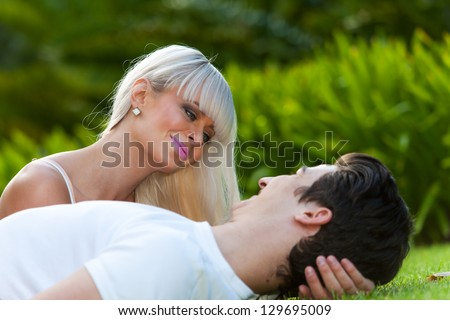 Close up portrait of happy couple laying on grass outdoors. - stock photo