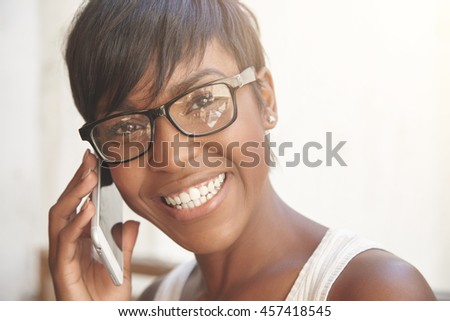 Close up portrait of happy dark-skinned woman with short pixie haircut wearing glasses, having phone conversation with cheerful look, smiling, showing her white teeth while talking to her boyfriend - stock photo