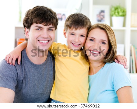 Close-up portrait of happy faces of smiling friendly young family with son - stock photo