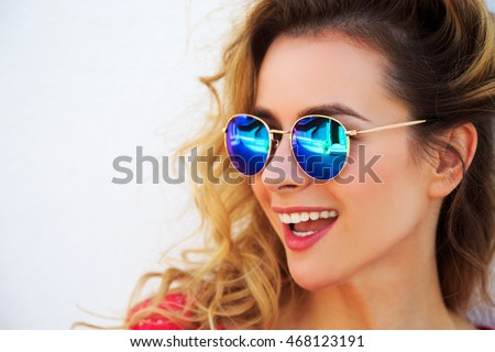 Close Up Portrait of Happy Fashion Woman in Sunglasses. Smiling Trendy Girl in Summer. White Wall Background Copy Space. Not Isolated Toned Photo.