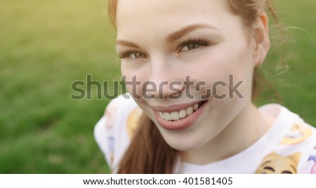 Close up portrait of happy girl sitting on grass at warm sunny day