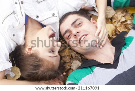 Close up portrait of Happy latin hispanic couple kissing and embracing lie on dry yellow autumn leaves in the fall park