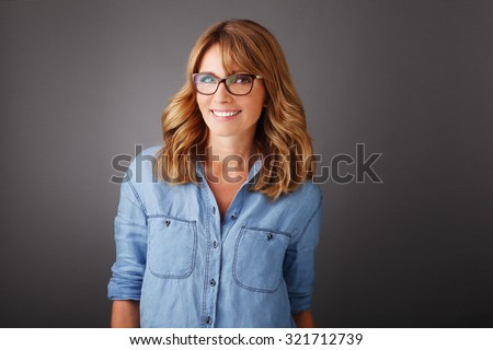 Close-up portrait of happy middle age woman standing at isolated background while looking at camera and smiling.
