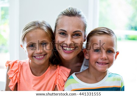 Close-up portrait of happy mother with children at home