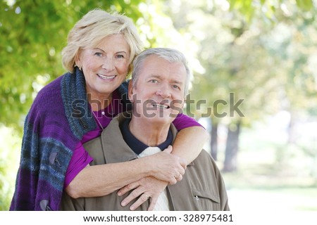 Close-up portrait of happy senior couple  smiling to the camera while relaxing at outdoor and elderly woman hugging old man.  - stock photo