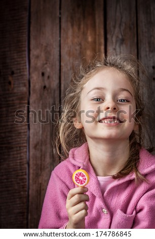 Close up portrait of happy smiling caucasian five years old blond child girl with fruity lollipop on rustic wooden background. Careless childhood, countryside. - stock photo